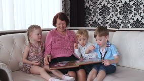 Grandmother with grandchildren looking photo album. Three grandchildren visiting their grandmother, sit on the couch and watch a photo album stock video