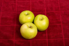 Three Granny Smith Apples on Red Towel Stock Image