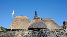 Three grass rooftops and Indonesian flag at Bena a traditional village with grass huts of Ngada people in Flores. Royalty Free Stock Photography