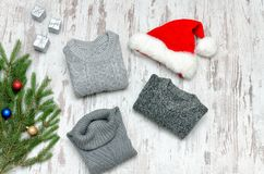 Three gray sweaters, Santa`s hat and fir branch on a wooden back Royalty Free Stock Photos