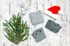 Three gray sweaters, Santa`s hat and fir branch on a wooden back stock photography