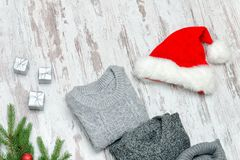 Three gray sweaters and Santa`s hat on a wooden background. Fash Stock Photos