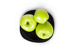 Three green apples on a black plate Royalty Free Stock Photos
