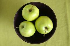 Three green apples inside purple bowl closeup. Three green apple inside purple bowl on green tablecloth top view close up Royalty Free Stock Photos