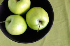 Three green apples inside purple bowl closeup. Three green apple inside purple bowl on green tablecloth top view close up Stock Images