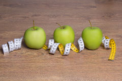 Three green apples and measure tape on table Royalty Free Stock Photo