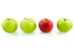 Three green apples with one red apple Stock Photos