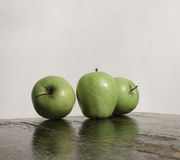 Three green apples and reflection on wood texture Royalty Free Stock Photos