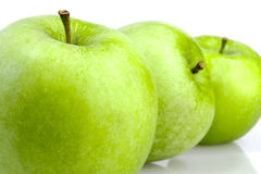 Three green apples in a row Stock Images