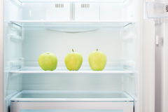 Three green apples on shelf of open empty refrigerator Royalty Free Stock Photography
