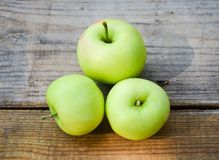 Three green apples on wooden boards royalty free stock photo