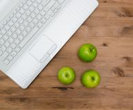 Three green apples on worplace Royalty Free Stock Photography