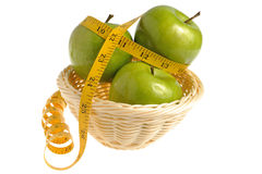 Three green apples wrapped with measuring tape in the wicker bas Royalty Free Stock Images