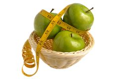 Three green apples wrapped with measuring tape in the wicker bas Stock Image