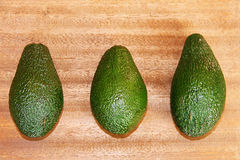 Three green avocados on a wooden background Royalty Free Stock Photography