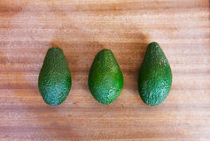 Three green avocados on a wooden background Royalty Free Stock Images