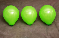 Three green balloons against brown wallpaper Royalty Free Stock Photo