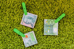 Three green banknotes in green clothes pegs at green background Stock Image