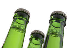 Three green bottle necks with crown caps Stock Photos