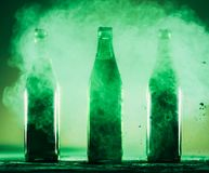 Three green bottles standing in a green dust. St. Patrick`s Day. Irish beverage Royalty Free Stock Photos