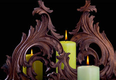 Three green candles. Three green candles among two wooden sculptures on a turkish surface and a black background Royalty Free Stock Photography