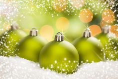 Three Green Christmas Ornaments on Snow Over an Abstract Background Royalty Free Stock Photography