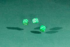 Three green dices falling on a green table. Three green dices falling on a isolated green table royalty free stock images