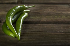 Three green hot chilli peppers on wood with copy space Royalty Free Stock Photography