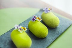 Three green mousse cakes covered with velvet glaze royalty free stock images