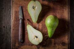 Three green pears on an old rustic box Stock Photos