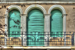 Three green roller blinds in an old italian balcony Royalty Free Stock Photos