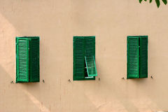 Three Green Shutters. Three bright green shutters on a flat, plain building royalty free stock photos
