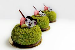 Three green textured pistachio desserts with edible pansy flowers and dried strawberries royalty free stock photo