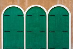 Three green wooden doors on brown concrete wall. Three green wooden arched top doors on brown concrete wall Stock Images