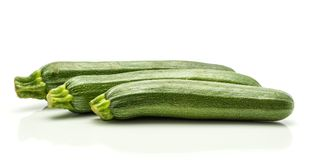 Fresh Green Zucchini isolated on white. Three green zucchini isolated on white background long raw courgettes in row Stock Photo