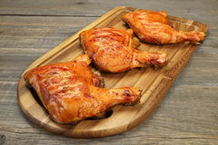 Three Grilled BBQ Chicken Leg Quarter On Wood Board. Three Grilled BBQ Crispy Chicken Leg Quarter On The Wood Board And Country Table In The Background, Top View Royalty Free Stock Images
