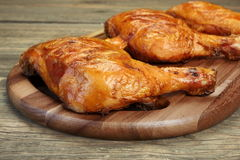 Three Grilled BBQ Chicken Leg Quarter On Wood Board. Three Grilled BBQ Crispy Chicken Leg Quarter On The Wood Board And Country Table In The Background, Top View Stock Photography