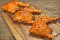 Three Grilled BBQ Chicken Leg Quarter On Wood Board. Three Grilled BBQ Crispy Chicken Leg Quarter On The Wood Board And Country Table In The Background, Top View Stock Photos
