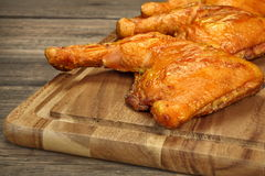 Three Grilled BBQ Chicken Leg Quarter On Wood Board. Three Grilled BBQ Crispy Chicken Leg Quarter On The Wood Board And Country Table In The Background, Top View Stock Images
