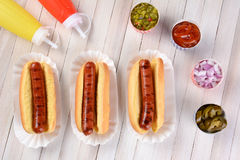 Three Grilled Hot Dogs. Ready to be garnished on a rustic wood picnic table. High angle view Royalty Free Stock Image