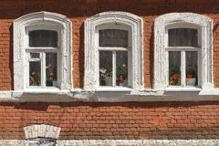 Three grunge windows with red brick wall Stock Images