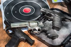 Three Guns and target on table outside stock photography