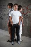 Three guys. Three boy standing close in front of graffiti wall royalty free stock images