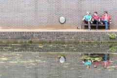 Three Guys Chatting Near Canal Royalty Free Stock Photos