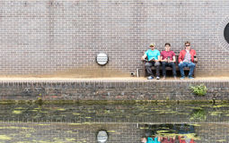 Three Guys Chatting Near Canal Stock Image