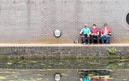 Three Guys Chatting Near Canal Stock Image