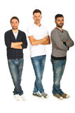 Three guys with hands and legs crossed. Three guys in a line standing with hands and legs crossed isolated on white background Stock Photo