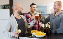 Three guys  at house party. Three american guys drinking beer and laughing at house party Stock Photo