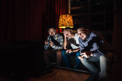 Three guys with joystick addicted to video game Royalty Free Stock Images