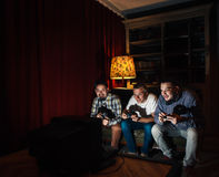 Three guys with joysticks addicted to video game Stock Photos